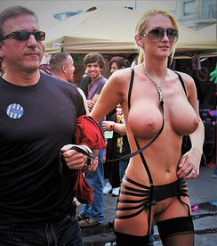 A submissive woman is paraded nude at Folsom Street Fair. She is wearing a leash, one end of which is held by her master.