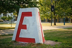 "The UBC Engineering Cairn, a chamfered tetrahedral concrete block with a large red ""E"" on each of its three sides, shown here in its unvandalised state. Painting the cairn is a favourite hobby of student clubs and rival faculties."