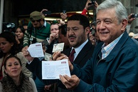 López Obrador (right) holding his Voter ID upside down along with Martí Batres (center) after submitting the formal political registration of MORENA to the INE
