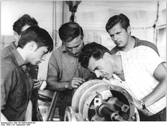 A master discusses a vacuum compressor with his apprentice and several other craftsmen