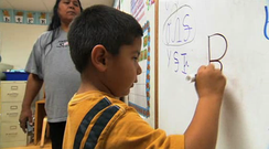 Oklahoma Cherokee language immersion school student writing in the Cherokee syllabary