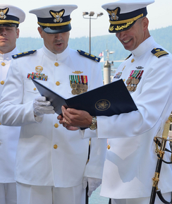 A Coast Guard chief warrant officer (CWO2, left) and an officer (commander, O-5, right) wearing Full Dress Whites