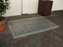 In-ground grease trap outside of a shop