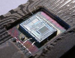 The die from an Intel 8742, an 8-bit microcontroller that includes a CPU running at 12 MHz, 128 bytes of RAM, 2048 bytes of EPROM, and I/O in the same chip