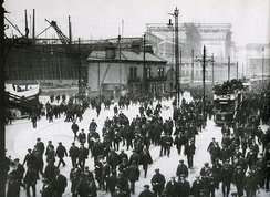 Workers leaving the shipyard at Queens Road in early 1911. RMS Titanic is in the background, beneath the Arrol Gantry. The bow of SS Nomadic is at the far left.