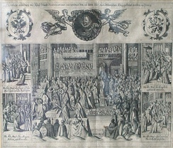 A bishop crowns a kneeling man in a large church filled with dozens of men