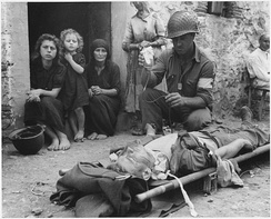 Wounded American soldier receiving blood plasma, Sicily, 9 August 1943.