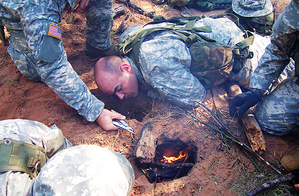 US Army aviation SERE students create a Dakota hole to conceal a fire in order to better protect their position from enemy observation.