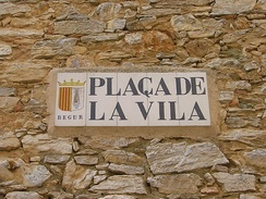 "Sign in the town square of Begur, Catalonia, Spain. In plaça de la vila (literally ""square of the town""), since the noun vila (""town"") is feminine singular, the definite article carries the corresponding form, la (""the"")."