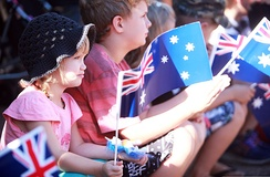 Children wave Australian flags during an Anzac Day parade in Palmerston