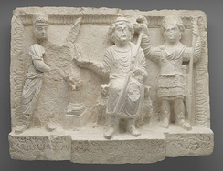 a relief depicting three figures. In the middle a deity sitting on a throne, to the right, a man (king Seleucus I) standing, and to the left a Palmyrene merchant is standing