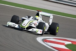a white and fluorescent green Formula One car drives around a corner