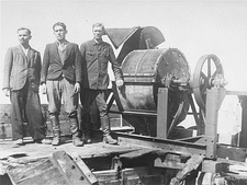 Jewish prisoners forced to work for a Sonderkommando 1005 unit pose next to a bone crushing machine in the Janowska concentration camp.jpg