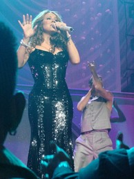 A bold woman is singing on stage. She wears a black dress that has many mirrors. Behind her, a man with a brown suit is seen.