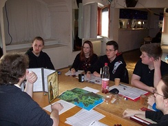 A group playing a tabletop RPG. The GM is at left using a cardboard screen to hide dice rolls from the players.