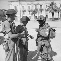 British troops of the 6th Battalion, Durham Light Infantry, part of the British 50th Division, with an American paratrooper of the 505th Parachute Infantry Regiment, part of the U.S. 82nd Airborne Division, in Avola, 11 July 1943.