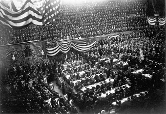 "A view inside the Interstate Exposition Building (known as the ""Glass Palace"") during the convention; James Abram Garfield (center, right) is on the podium, waiting to speak."