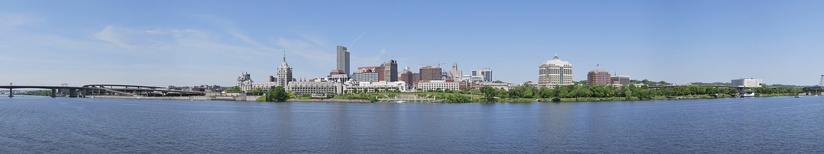 The state capital Albany and the Hudson River from Rensselaer. At the left foreground is the System Administration Building of the State University of New York. The tallest skyscraper visible is one of several buildings in the Empire State Plaza governmental complex.