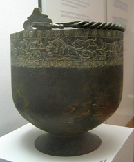 Large black bowl-shaped bucket on a stand. The bucket has incrustation around its top.