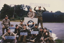 Personnel of the 359th Fighter Group with the insignia of the 370th Fighter Squadron and signage that has been taken down at East Wretham during the V-E Day celebration, 7 May 1945