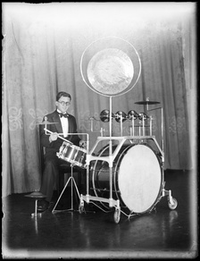 "Dance band drummer Stan Farmer in 1935 at Mark Foy's Empress Ballroom in Sydney, New South Wales, using a kit with bass drum pedal and a ""low sock"""