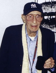 Eddie Layton wearing a New York Yankees cap and holding a mug