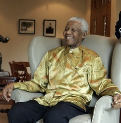 "Mandela on a visit to Australia in 2009; he is wearing one of the brightly coloured garments that became known as ""Madiba shirts"""