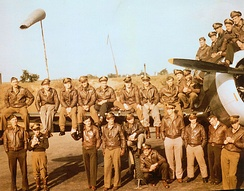 A large group of 4th Fighter Group pilots sitting on or standing in front of a P-47 Thunderbolt at Debden air base. The 4th Fighter Group flew P-47 Thunderbolts on missions between March 1943 and February 1944.