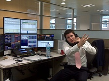 A stockbroker using multiple screens to stay up to date on trading