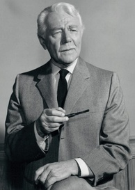 A black-and-white photograph of a man in a suit and tie with white hair and a pipe