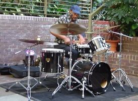 "South African jazz drummer Louis Moholo playing a four-piece kit. One of the conventions of drum kit playing is that the number of ""pieces"" in a kit only counts the drums, not the cymbals or other percussion instruments."