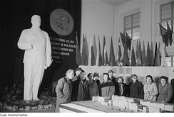 Workers inspect architectural model under a statue of Stalin, Leipzig, East Germany, 1953.