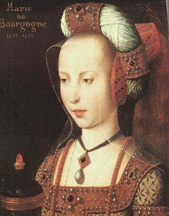 Mary of Burgundy wears a headdress comprising a truncated-cone hennin, a jewelled padded roll, and a sheer veil.