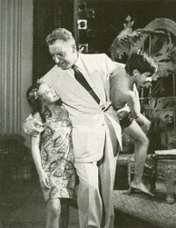 Pinza, in a white suit, walks along holding a mixed-race boy, about 7 or 8 years old, while listening to a slightly older girl who walks next to him.
