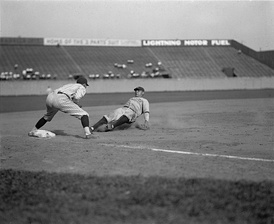Babe Ruth sliding into third base at Griffith Stadium in Washington, D.C., on June 23, 1925. Washington Senators third baseman Ossie Bluege looks on.