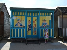 A child examines a decorated beach hut on Mablethorpe's seafront