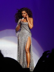 Knowles performing during The Beyoncé Experience dressed in sparkly and silvery dresses. The wardrobe of the tour received positive reception from critics, many of whom praised her overall look.