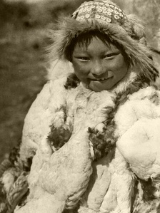Nunivak Cup'ig child wearing bird skin clothing (parka?) and wood knot-like beaded circular cap (uivqurraq), photograph by Edward Curtis, 1930