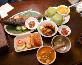 Example of Indonesian Sundanese meal; ikan bakar (grilled fish), nasi timbel (rice wrapped in banana leaf), ayam goreng (fried chicken), sambal, fried tempeh and tofu, and sayur asem; the bowl of water with lime is kobokan.