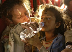 A soldier gives a young Pakistani girl a drink of water as they are airlifted from Muzaffarabad to Islamabad.