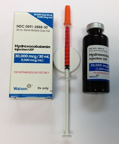 A vitamin B12 solution (hydroxycobalamin) in a multi-dose bottle, with a single dose drawn up into a syringe for injection. Preparations are usually bright red.