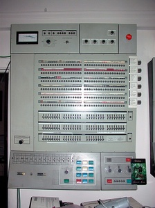 "System/360 Model 65 operator's console, with register value lamps and toggle switches (middle of picture) and ""emergency pull"" switch (upper right)"