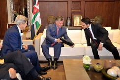 King Abdullah II shows his son, Crown Prince Hussein, a photo given to them by the then United States secretary of state John Kerry.