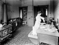 Mrs. Arthur Beales in the kitchen of the Beales home, Toronto, Ontario, Canada, circa 1903–1913. Note the water pipes along the back wall that fed the sink