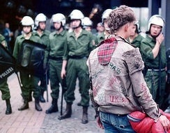 A punk faces a line of riot police at a 1984 protest in Germany