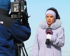 A television reporter speaking into a microphone in front of a camera, 2005