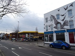 Petrol station at the site of 517 High Road, Leytonstone, where Hitchcock was born; commemorative mural at nos. 527–533 (right).[21]