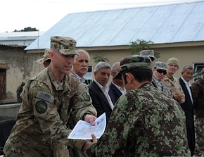 U.S. Air Force Col. David Tabor, left, the commander of the 438th Air Expeditionary Advisory Group, gives a certificate to an Afghan National Army Air Force airman during a graduation ceremony 111013-F-RW714-065.jpg