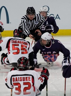 Ice Sledge Hockey: United States (blue shirts) vs Japan (white shirts) during the 2010 Paralympics in Vancouver.