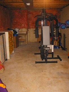 An unfinished basement used for storage and exercise